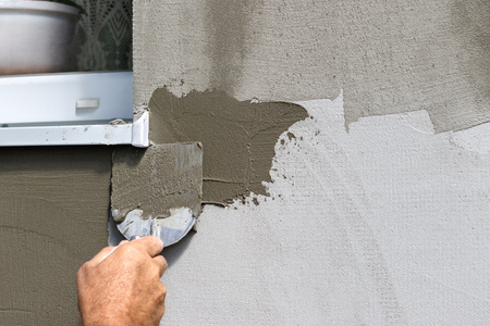 Mans hand applying fresh spackling paste to exterior wall