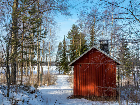 The old bathhouse in the woods by the lake, clear winter day. Editorial