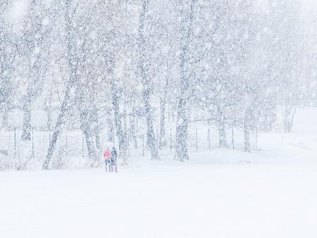 People walking along the frozen lake in heavy snow