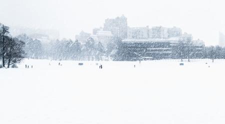 People walking on the frozen lake in heavy snow.