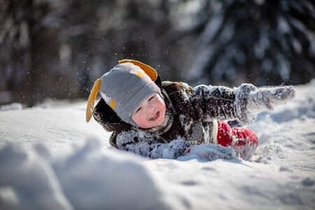 A little handsome boy in red pants and a brown sheepskin coat makes his way through the snowdrifts of snow. The child is being played. Trees in the snow in the background.