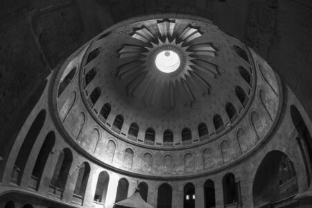 Dome in the Church of the Holy Sepulcher. The old city of Jerusalem. Black and white photo. A ray of light penetrates the temple. Black and white photo. Stock Photo