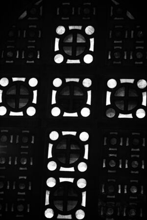 Stained glass in the form of a cross. Black and white photo.