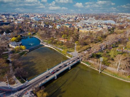 Top view on Secheni baths, Budapest city park. People are resting on the green grass. Lakes and bridge in the park. Spring. Trees without leaves and with green leaves.