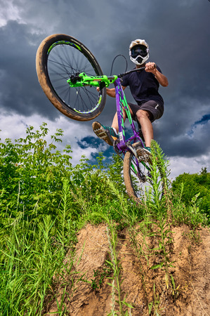 Moscow, Russia - July 6, 2017: Mountain bike cyclist doing wheelie stunt on a mtb bike. Biker riding extreme sport bicycle. Cool athlete cyclist on a bike. MTB biking.