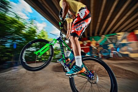 Moscow, Russia -  August 10, 2017: Mountain bike cyclist doing wheelie stunt on a mtb bike. Mountain cyclists doing wheelie stunt on a mtb bike. Biker riding extreme sport bicycle. Cool athlete cyclist on a bike. MTB biking. Close up.