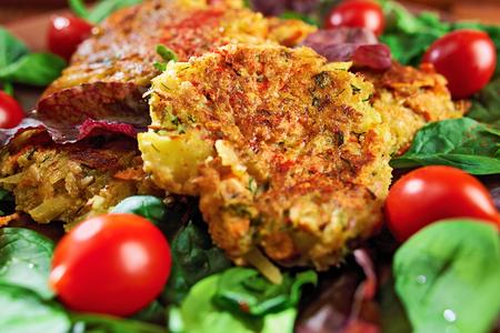 토마토와 나무 배경에 그린 샐러드와 함께 접시에 제공하는 감자와 렌즈 콩에서 만든 채소 햄버거; 닫다. 스톡 콘텐츠
