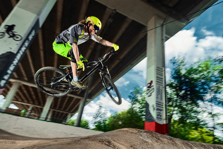 mtb: Moscow, Russia - August 10, 2017: Jump and fly on a mountain bike. Rider in action at mountain bike sport. Biker making a stunt and step down jumping. Cool athlete cyclist on a bike. MTB biking. Editorial