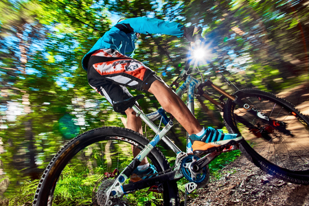 Moscow, Russia - August 24, 2017: Biker riding with aggressive turns. Mountain Bike cyclist riding in forest. Rider in action at mountain bike sport. MTB biking.