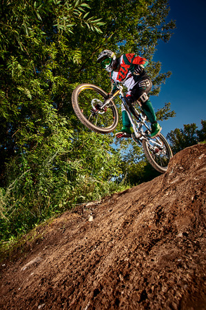 Moscow, Russia -  August 31, 2017: Mountain bike cyclist doing wheelie stunt on a mtb bike. Biker riding extreme sport bicycle. Cool athlete cyclist on a bike. MTB biking.