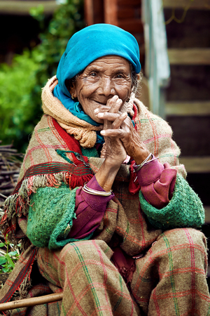 Naggar (Kullu Valley), North India - July 2013. Old rural Indian woman sitting in the courtyard of his house. Smiling at the camera.