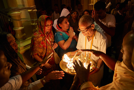 People getting blessings from the holy fire during the morning darshan inside the Sri Krishna Balaram Mandir temple, ISKCON temple of Vrindavan. Uttar Pradesh, India. - July 2017. Editorial
