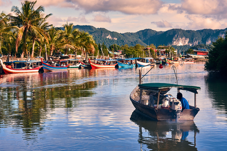 Ein lokaler Fischer fährt mit einem Boot vom Bootspark zum Meer, um dort zu angeln. Traditionelle bunte asiatische Fischerboote im Fischerdorf. Langkawi Insel, Malaysia. Standard-Bild - 92547874