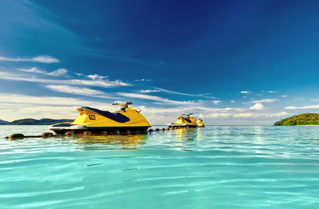Yellow Jet ski on the sea and blue sky and small islands in background. Stockfoto