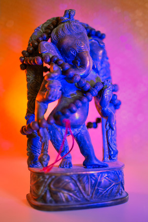 Hindu God - Lord Ganesha with rudraksha rosary in a colorful light. Colorful photo of deity Ganesha whit blured background.