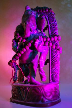 Hindu God - Lord Ganesha with rudraksha rosary in a colorful light. Colorful photo of deity Ganesha whit blured background.