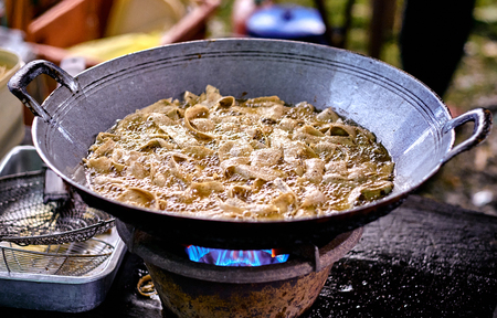 Fried chips in oil at wok. Asian, Indian and Chinese street food. Food court on local market of Langkawi island, Malaysia.Traditional asian street food. Stock Photo