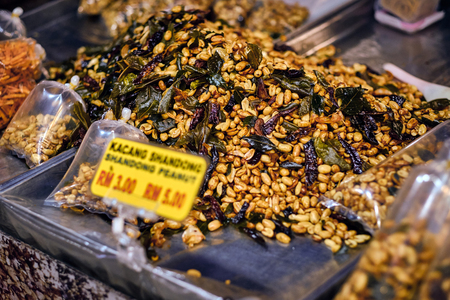 Fried peanut with chilly pepper - traditional asian street food. Asian, Indian and Chinese street food. Food court on local market of Langkawi island, Malaysia.
