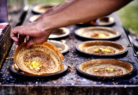 Cooking traditional asian pancakes. Indian and Chinese street food. Food court on local market of Langkawi island, Malaysia. Traditional asian street food. Stock Photo