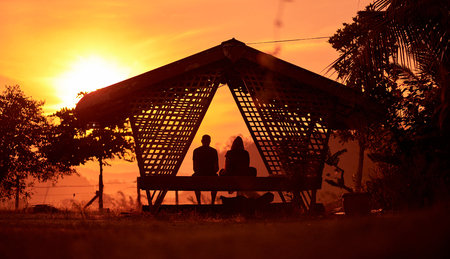 Romantic couple in love sitting together on terrace swing at sunset, silhouettes of young man and woman on holidays or honeymoon. Langkawi island, Malaysia.