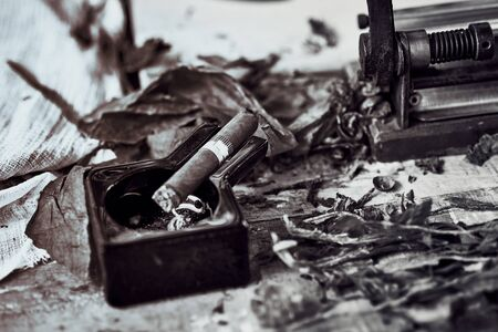close up of a Cuban cigar and a black ceramic ashtray on the wooden table whit dried and cured tobacco leaves. bw image