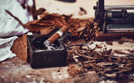 primo piano di un sigaro cubano e di un posacenere in ceramica nera sul tavolo di legno con foglie di tabacco essiccate e stagionate.