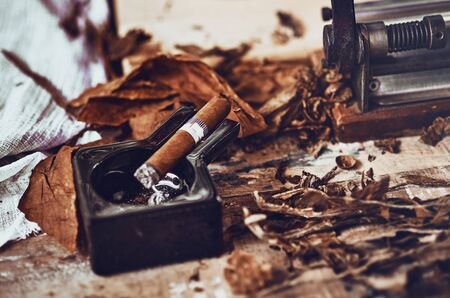 close up of a Cuban cigar and a black ceramic ashtray on the wooden table whit dried and cured tobacco leaves. Фото со стока