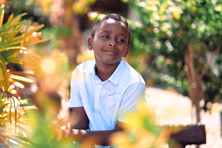 Kuala Lumpur, Malaysia - Jul, 2019: Closeup portrait of smiling young attractive African boy in park. 報道画像