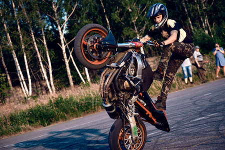 Moscow, Russia - Jul 12, 2020: Moto rider making a stunt on his motorbike. Stunt motorcycle rider performing motorcycle show. Motorcyclist making doing a difficult and dangerous stunt on his motorbike Redakční