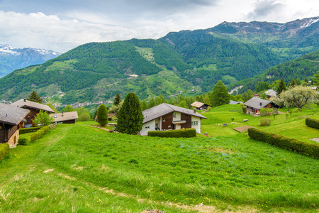 RIDDES, SWITZERLAND - MAY 2015: Panorama of village on a green meadow at sunny day in the Alps