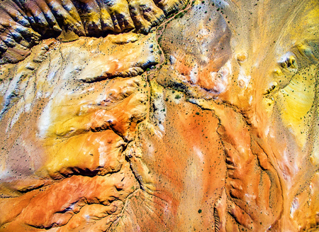 Aerial shot of the textured yellow mountains resembling the surface of Mars