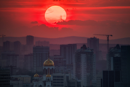 Ekaterinburg, Russia - Jule, 2018: Telephoto lens panoramic shot of cityscape view megalopolis during sunset with giant sun at summer evening