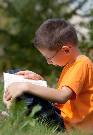 Boy reading a book on a summer day