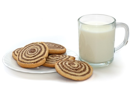 black and white cookies on the plate with cup of milk