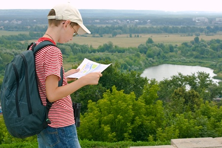 Boy with binoculars and backpack looks at the map on a hike