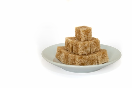 cubes of brown sugar on white plate, isolated on white