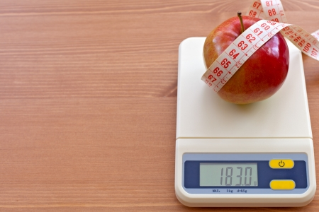 red apple with measure tape on electronic scale, diet concept  Stock Photo - 14334284