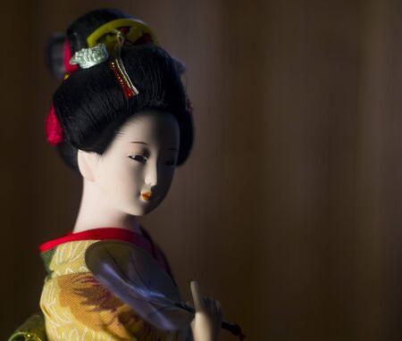 Japanese geisha doll on brown background