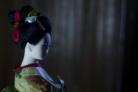 Japanese geisha doll at night on brown background