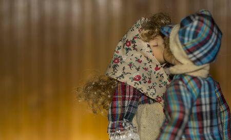 Couple of dolls kissing outside