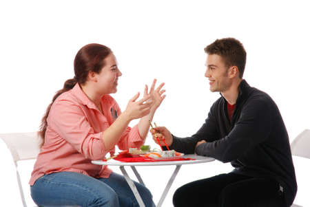 Boy and girl talking and eating sushi photo