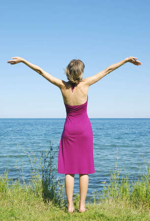 One girl in purple dress standing on the sea shore Stock Photo