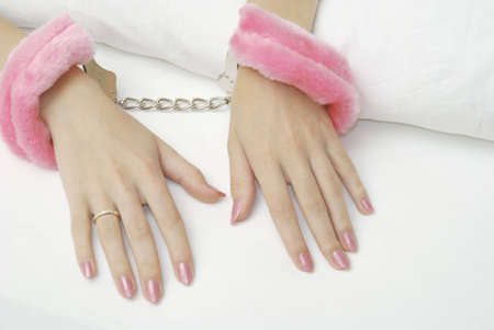 cuffs: Beautiful female hands locked in the pink handcuffs on the sheets Stock Photo