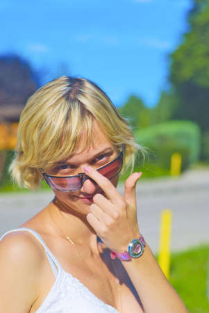 Beautiful girl touching her glasses - an outdoor picture