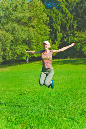 Beautiful young woman jumping over the green grass Stock Photo