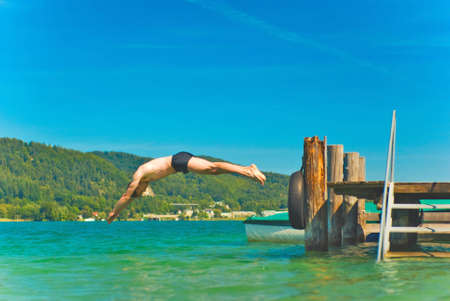 Diving man in a beautiful lake photo