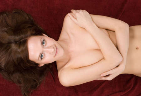 Young brunette covering her breast with her hair spread widely Stock Photo