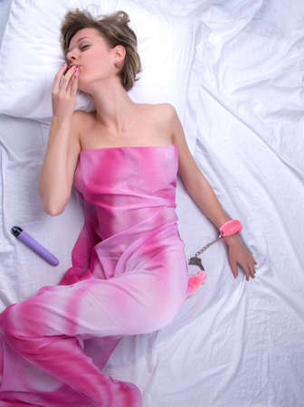 Young woman on bed with strawberry and sex toys Stock Photo