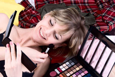 Young woman doing make-up on the stack of clothes