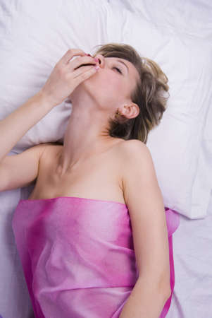 Young woman lying down with sex toys on a bed Stock Photo - 7556715